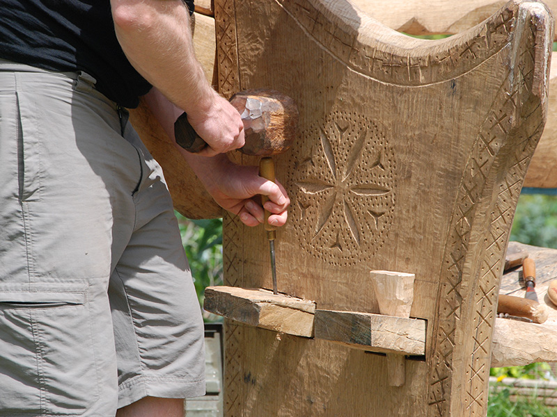 wood carving by a volunteer making the benches